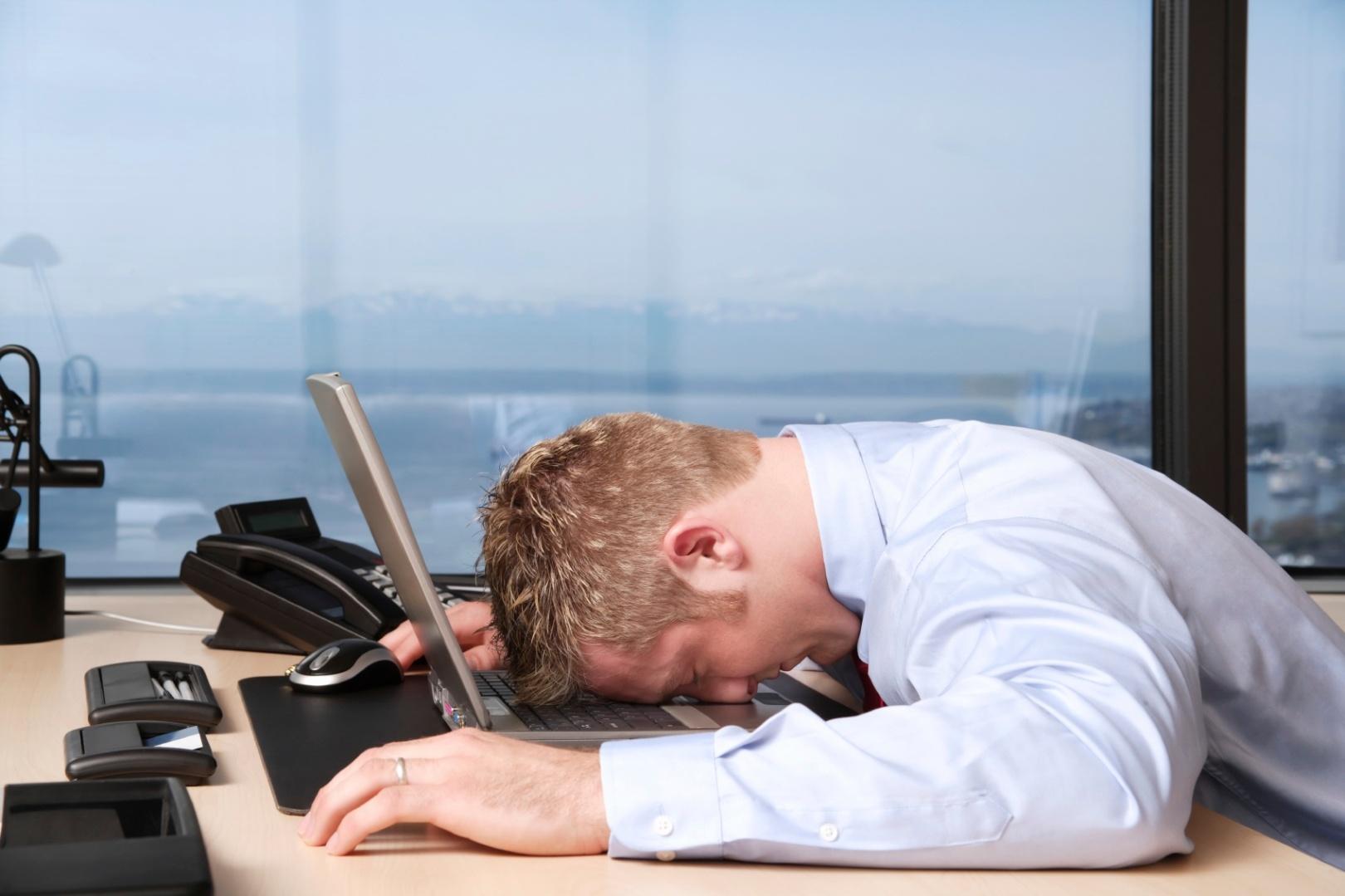 Man-sleeping-at-desk-on-laptop