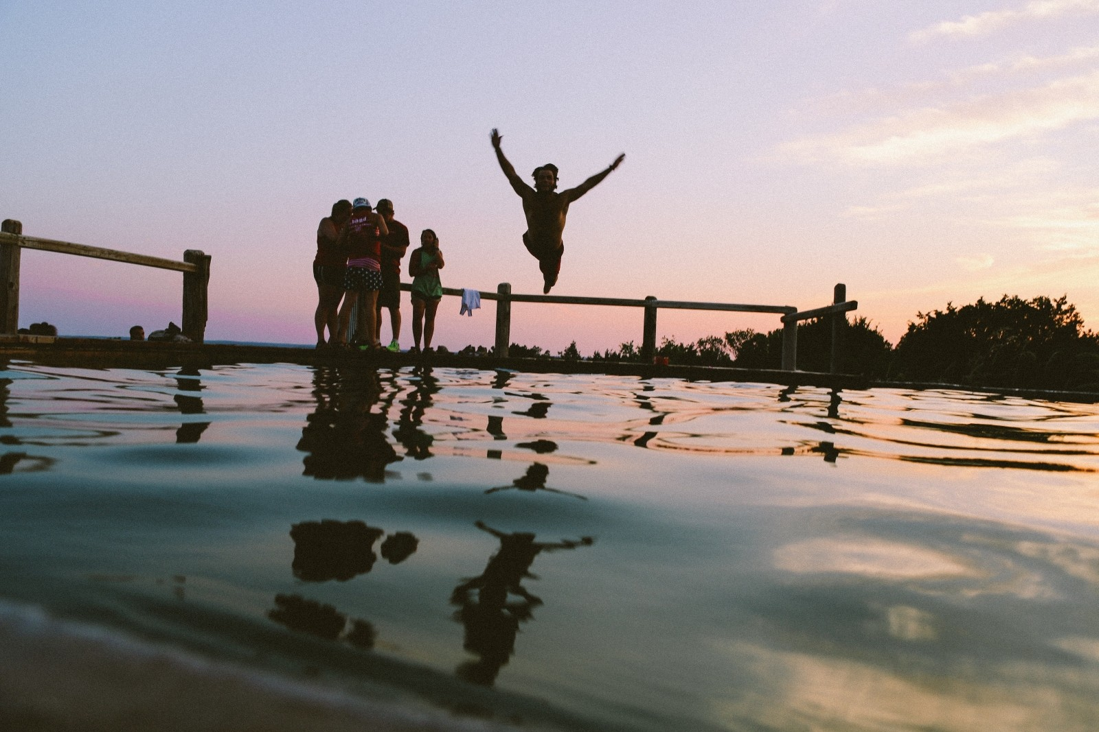 silhouette-of-friends-jumping-into-sea