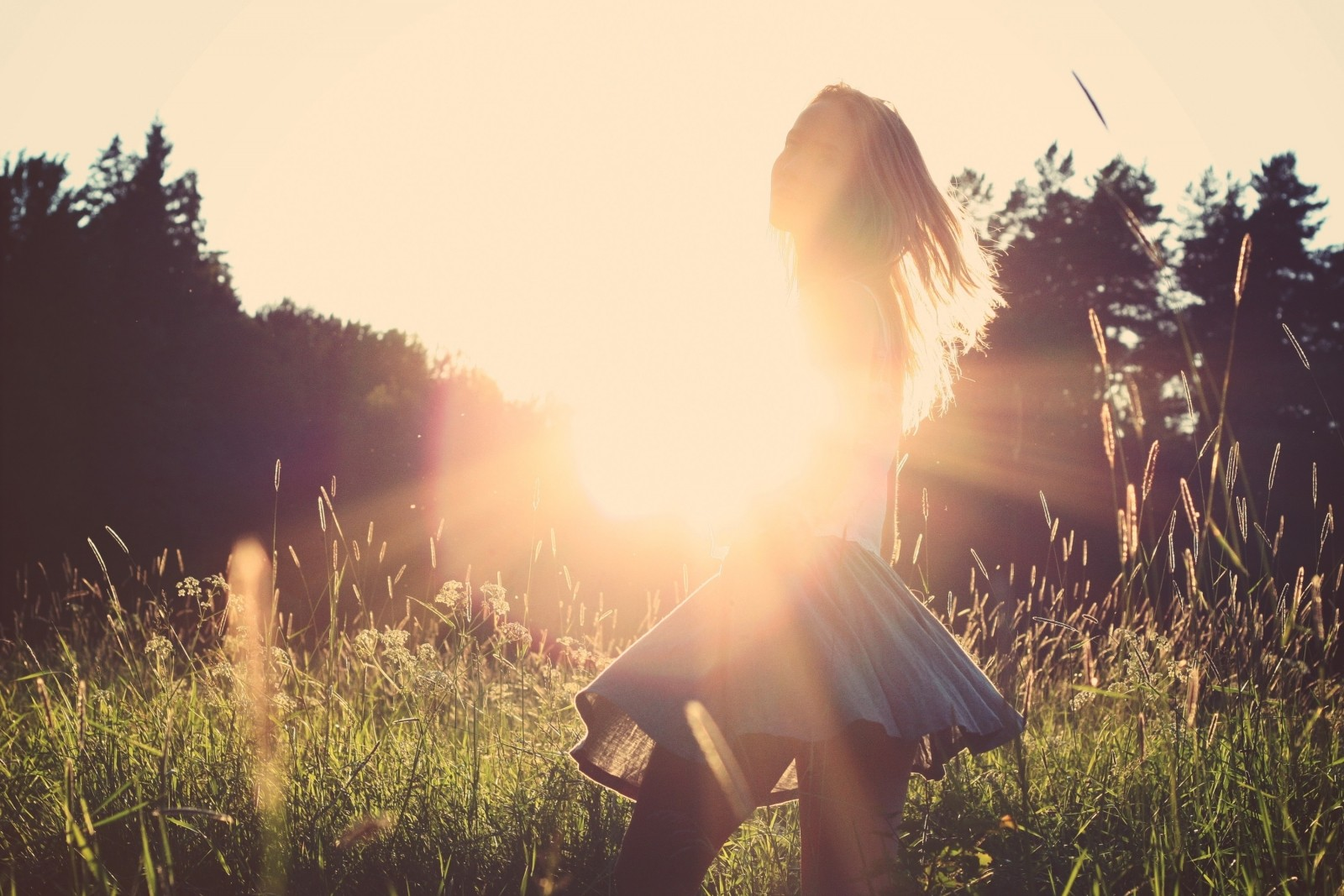 young-woman-standing-in-meadow-at-sunset