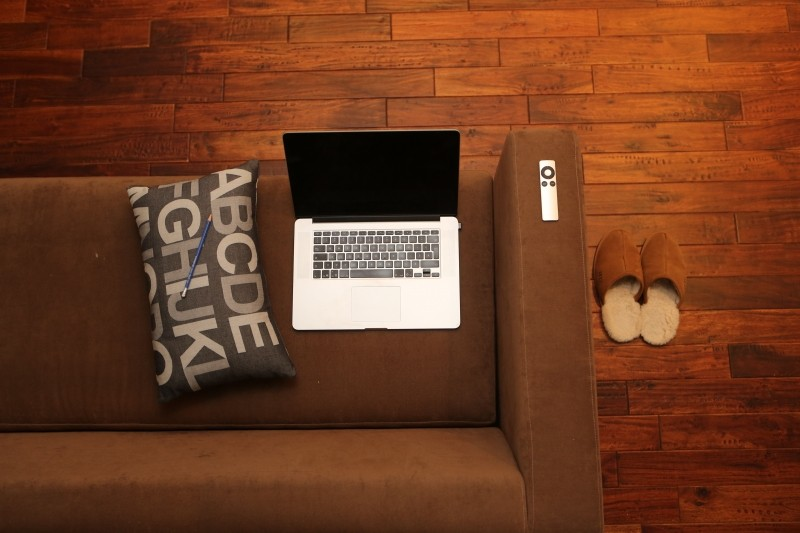 aerial-view-of-laptop-and-tv-remote-on-sofa