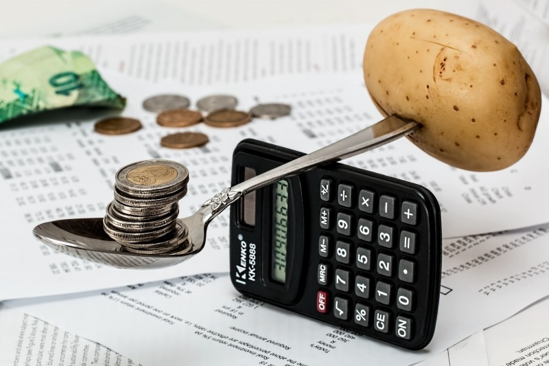 coins-on-spoon-with-potato-and-calculator