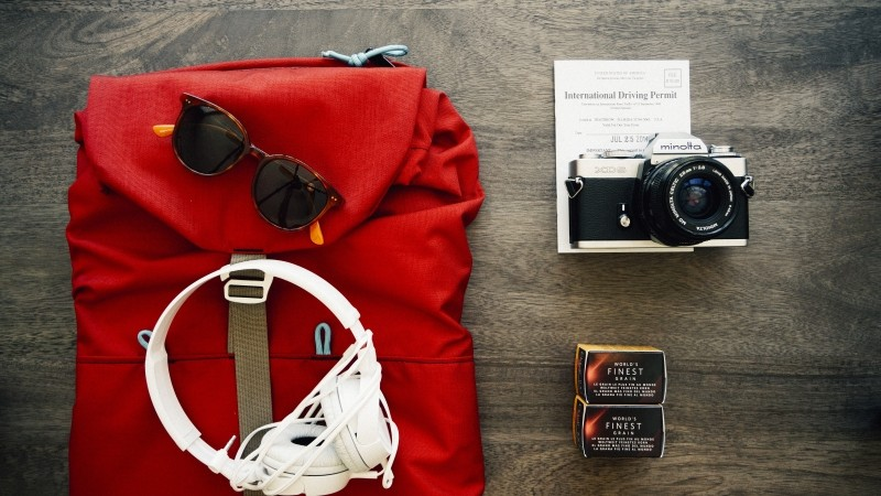 aerial-view-of-red-backpack-with-sunglasses-headphones-and-camera
